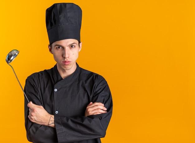 Серьезный молодой блондин мужчина-повар в униформе шеф-повара и кепке, стоя с закрытой позой, держа ковш, глядя в камеру, изолированную на оранжевой стене с копией пространства