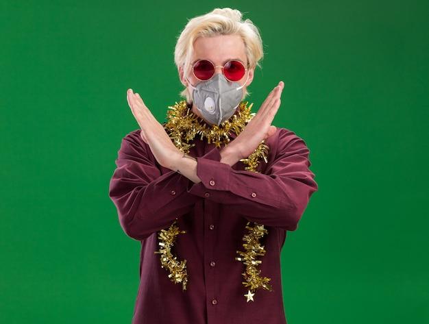 Grave giovane uomo biondo con gli occhiali e maschera protettiva con la ghirlanda di orpelli intorno al collo che non fa alcun gesto isolato sulla parete verde