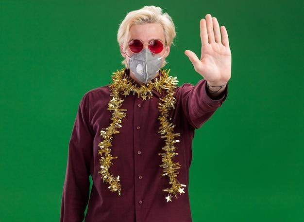 Grave giovane uomo biondo con gli occhiali e maschera protettiva con la ghirlanda di orpelli intorno al collo facendo gesto di arresto isolato sulla parete verde