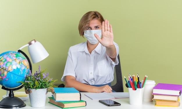 Grave giovane studentessa bionda che indossa una maschera protettiva seduta alla scrivania con gli strumenti della scuola che guarda l'obbiettivo che fa il gesto di arresto isolato sul muro verde oliva