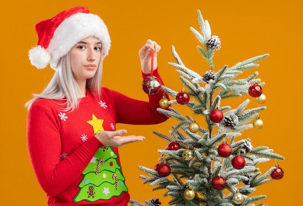 Grave giovane donna bionda in maglione di natale e santa hat tenendo palla di natale presentandolo con il braccio della sua mano in piedi accanto a un albero di natale su sfondo arancione