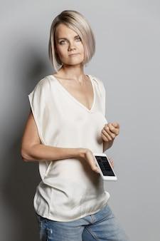 Серьезная молодая блондинка с телефоном в руке.