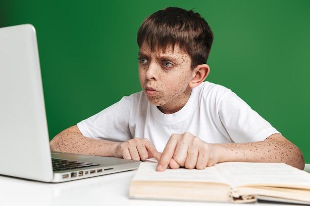 緑の壁の上の本とテーブルのそばに座っている間ラップトップコンピューターを使用してそばかすのある深刻な少年