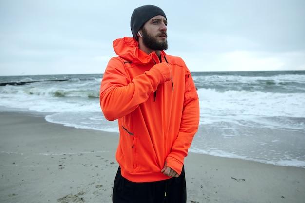 真面目な若いブルネットのひげを生やしたスポーツマンは眉を眉をひそめ、寒い曇りの天気で海辺に立って、彼の運動オレンジ色のコートを圧縮しながら先を見据えています