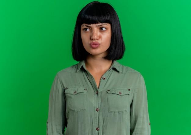 La ragazza caucasica castana giovane seria esamina il lato isolato su priorità bassa verde con lo spazio della copia