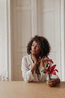 Serious young brunette curly dark-skinned woman in white blouse looks away, leans on wooden table and holds vase with red flowers