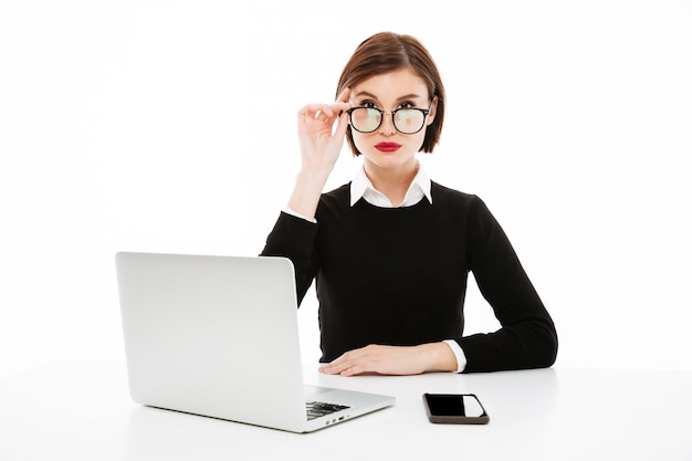 Serious young business lady wearing glasses using laptop computer
