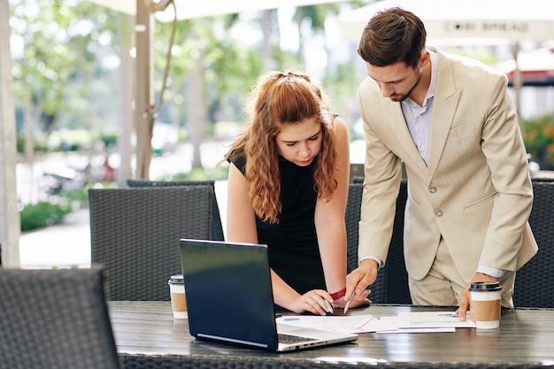 Серьезные молодые деловые люди склоняются над столом и обсуждают детали финансового отчета за чашкой кофе в летнем кафе