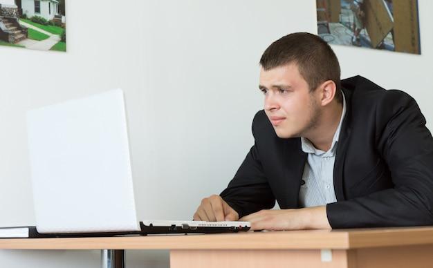 그의 나무 책상에 그의 노트북 컴퓨터를 탐색 하는 심각한 젊은 사업가