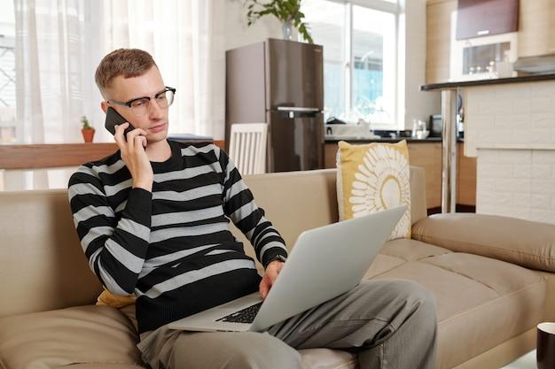 Серьезный молодой бизнесмен в очках, сидя на диване у себя дома, разговаривает по телефону и читает документ на экране ноутбука