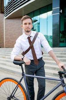 Серьезный молодой бизнесмен смотрит на вас, опираясь на велосипеде против лестницы и фасада здания