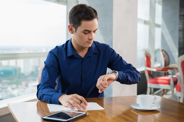 Serious young businessman looking at wrist watch