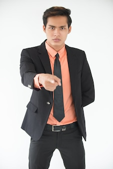 Serious young businessman pointing at camera