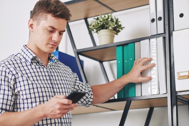 Серьезный молодой бизнесмен, читающий текстовое сообщение от коллеги на экране смартфона при поиске определенной папки в архиве
