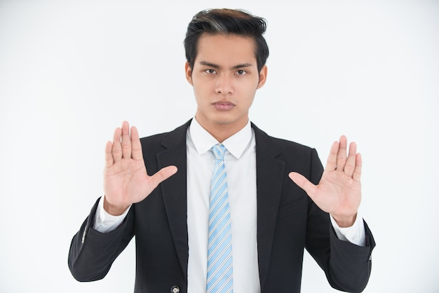 Serious young businessman showing open palms