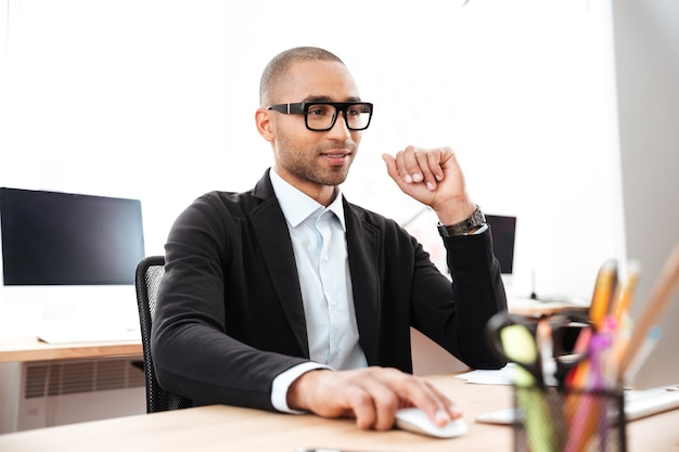 Serious young businessman sitting at the office and using pc