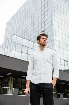 Serious young businessman standing in the city