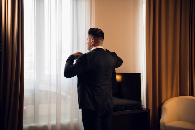 Serious young businessman standing near the window in his bedfoom, fixing his jacket, getting ready to go out