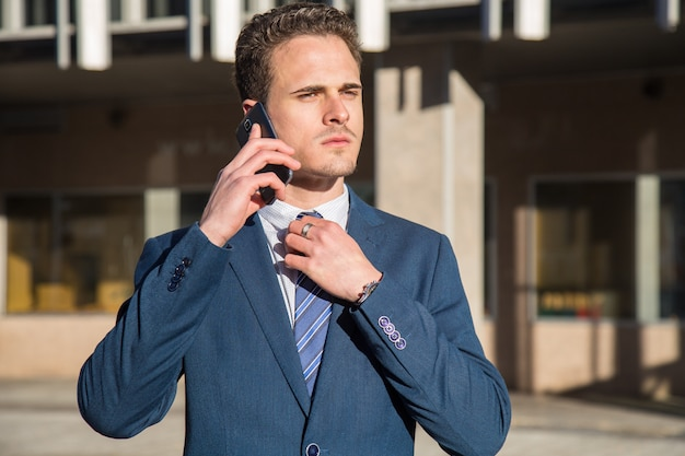 Serious young businessman talking on phone.