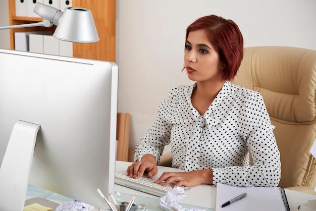 コンピューターの画面でレポートやメールを読んで答えを入力する深刻な若い実業家