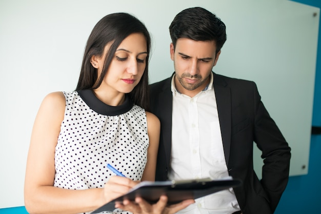 Serious young businesswoman showing documents to male executive