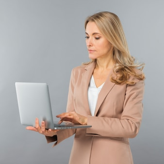 Serious young businesswoman using laptop on her hand against gray backdrop