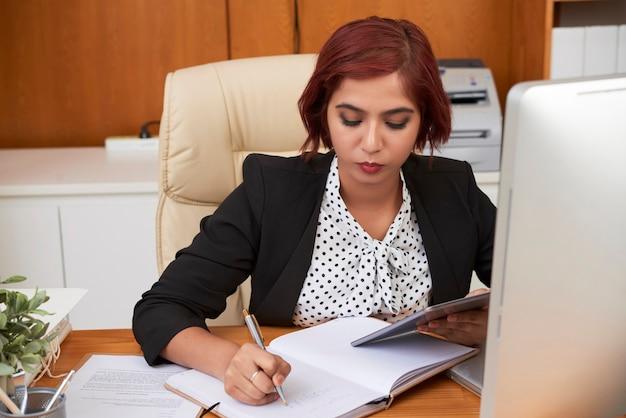 オンラインでドキュメントを読み、プランナーでメモを取るデジタルタブレットを持つ深刻な若い実業家