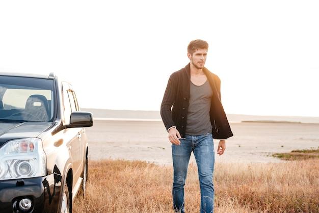 해변에서 그의 차 근처를 걷고 있는 진지한 젊은 캐주얼 남자