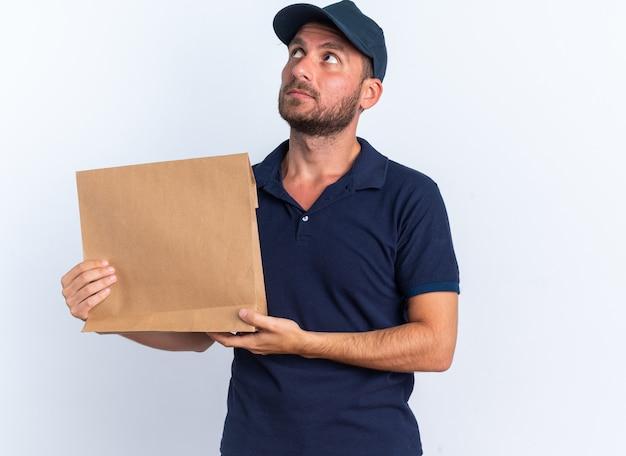 Grave giovane fattorino caucasico in uniforme blu e cappuccio che tiene il pacchetto di carta guardando in alto isolato sul muro bianco
