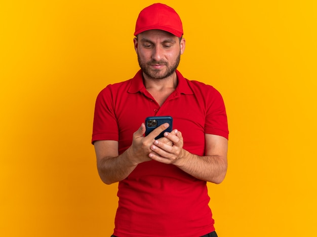 빨간 제복을 입은 백인 배달원, 모자를 들고 복사공간이 있는 주황색 벽에 격리된 휴대전화를 보고 있다