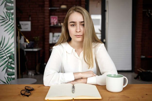 開いたノート、メガネ、マグカップを持って机に座って、新しい記事に取り組んでいる間、メモをとっている深刻な若い白人女性ブロガー。人、ライフスタイル、仕事、職業、創造性の概念