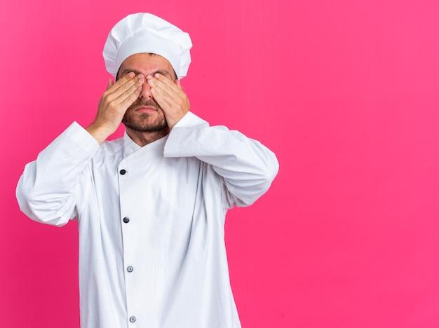Serio giovane maschio caucasico cuoco in uniforme da chef e berretto che copre gli occhi con le mani isolate sulla parete rosa con spazio copia
