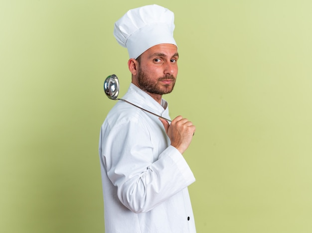 Serious young caucasian male cook in chef uniform and cap standing in profile view holding ladle on shoulder looking at camera isolated on olive green wall with copy space