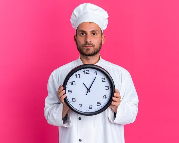 Серьезный молодой кавказский мужчина-повар в униформе шеф-повара и кепке держит часы