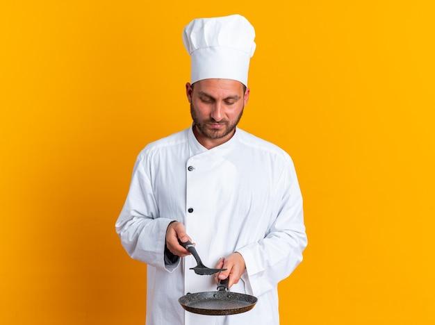 Серьезный молодой кавказский мужчина-повар в униформе шеф-повара и кепке держит сковороду и лопатку над ней, глядя на них