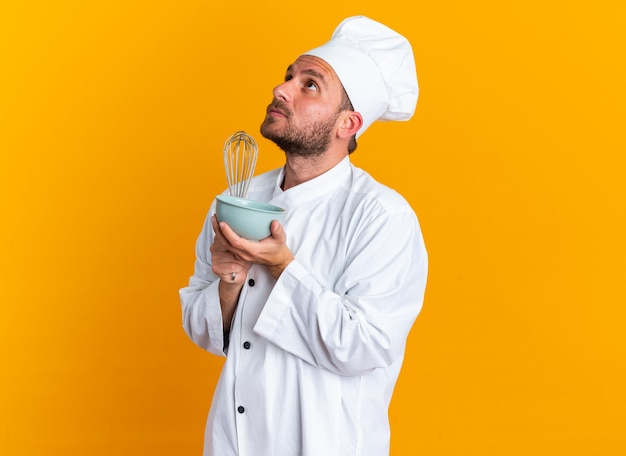 シェフの制服を着た真面目な若い白人男性料理人と、コピースペースのあるオレンジ色の壁に孤立して見上げる泡立て器とボウルを保持している縦断ビューで立っているキャップ