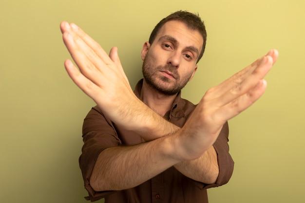 Grave giovane uomo caucasico che guarda l'obbiettivo che non fa alcun gesto isolato su sfondo verde oliva
