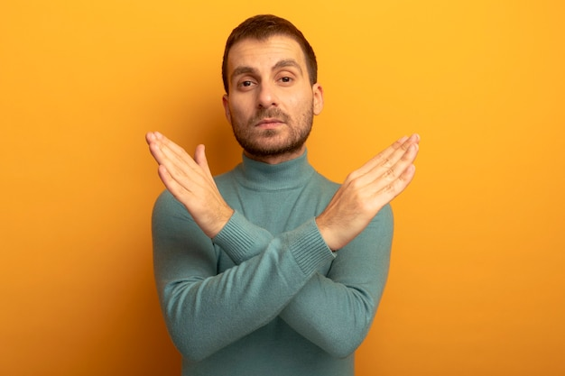 Serious young caucasian man looking at camera doing no gesture isolated on orange background with copy space