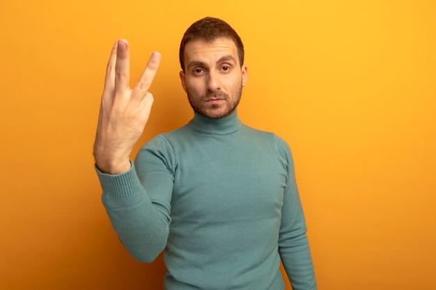 복사 공간 오렌지 벽에 고립 된 손으로 3을 보여주는 심각한 젊은 백인 남자