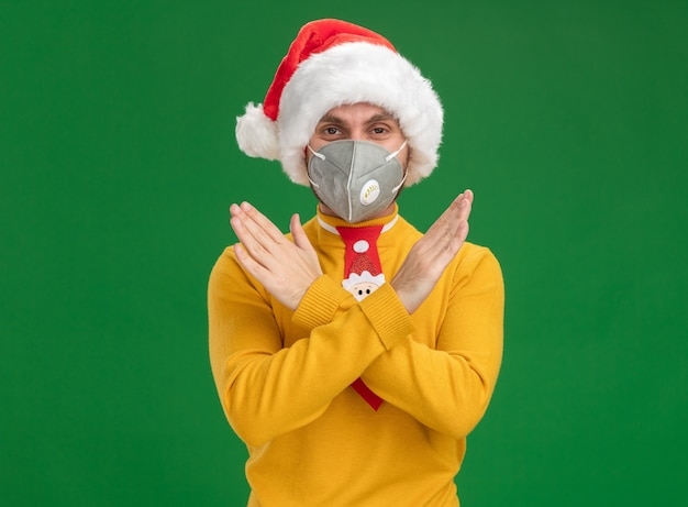 Serious young caucasian man wearing christmas hat and tie with protective mask looking  doing no gesture isolated on green wall with copy space