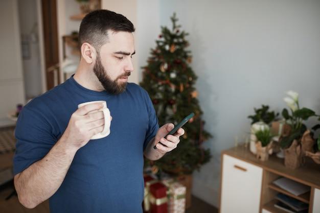 Серьезный молодой кавказский мужчина с бородой стоит с кружкой в гостиной с елкой и чек ...