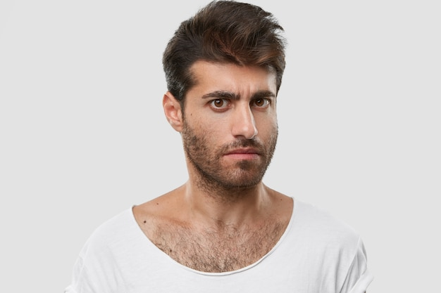 Serious young caucasian man with dark thick stubble, trendy haircut, casual clothes, models against white space