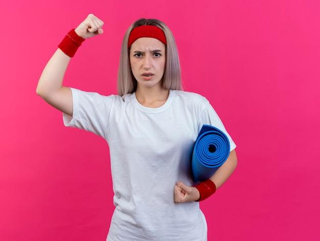 Giovane ragazza sportiva caucasica seria con le parentesi graffe che portano la fascia