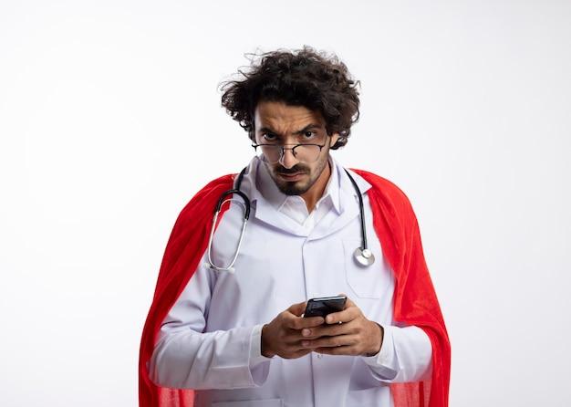 赤いマントと聴診器を首にかけた医者の制服を着た光学ガラスの深刻な若い白人のスーパーヒーローの男は電話を保持し、白い壁に孤立しているように見えます