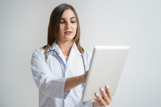 Serious young caucasian woman in lab coat looking at tablet