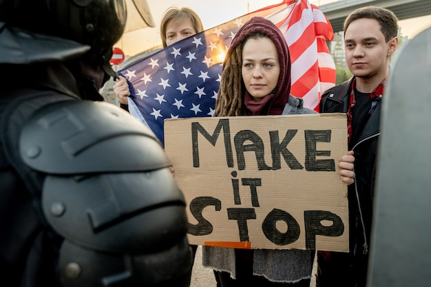 야외 경찰 앞에서 다른 활동가들과 함께 서 있는 make stop words가 있는 현수막을 들고 겁을 먹고 있는 진지한 젊은 백인 여성