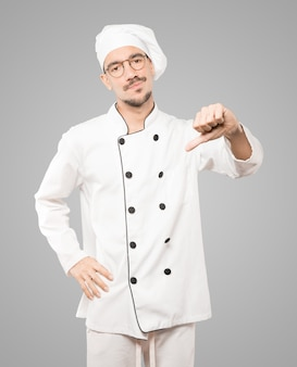 Serious young chef doing a gesture of defeated