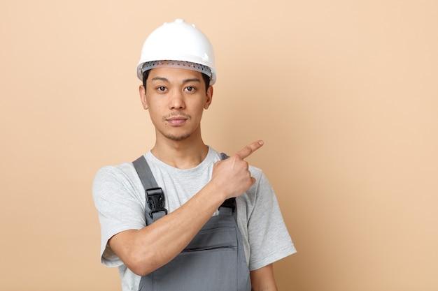 Grave giovane operaio edile che indossa il casco di sicurezza e uniforme che punta a lato