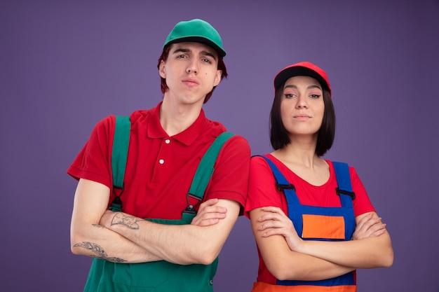Coppia giovane seria in uniforme da operaio edile e berretto in piedi con postura chiusa guardando la telecamera isolata sul muro viola