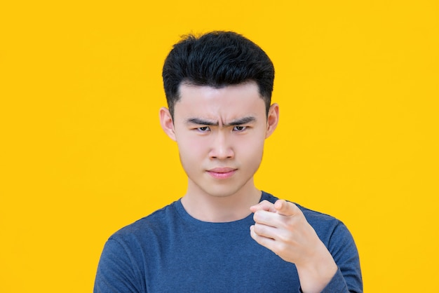 Serious young cute asian boy pointing finger at you